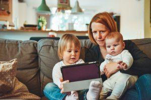 Ofsted registered childminder or parent teaches children on a tablet.