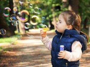 Child blows bubble in childcare.