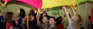 Preschool children play with a parachute.
